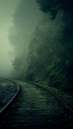 Railroad through the foggy valley