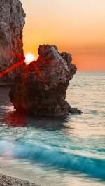 Sunset through the rocks beach